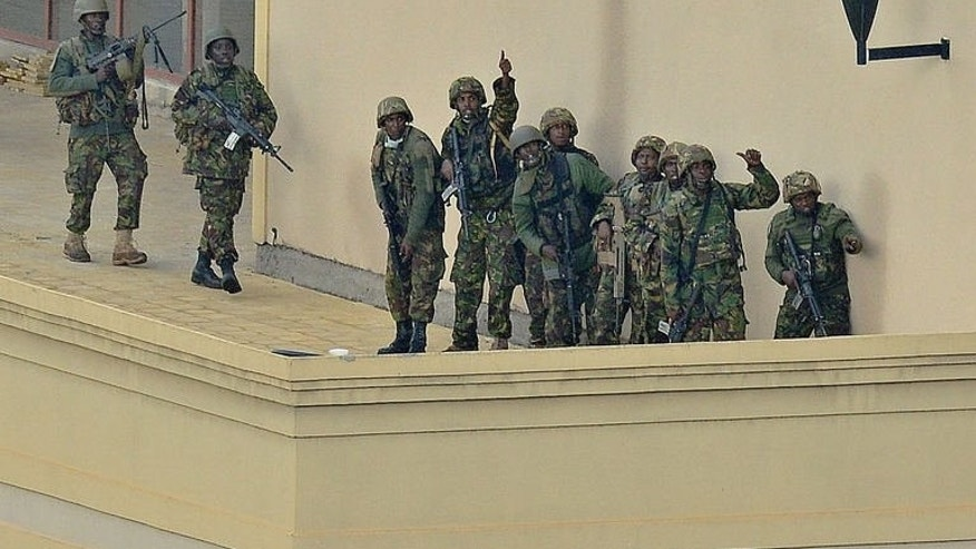 "A Kenyan soldier gives the thumbs up signal on September 24, 2013 after clearing the Westgate mall in Nairobi. Kenyan President Uhuru Kenyatta announced that a four-day siege by Islamist gunmen of a Nairobi shopping mall was over, with the ""immense"" loss of 61 civilians and six members of the security forces."