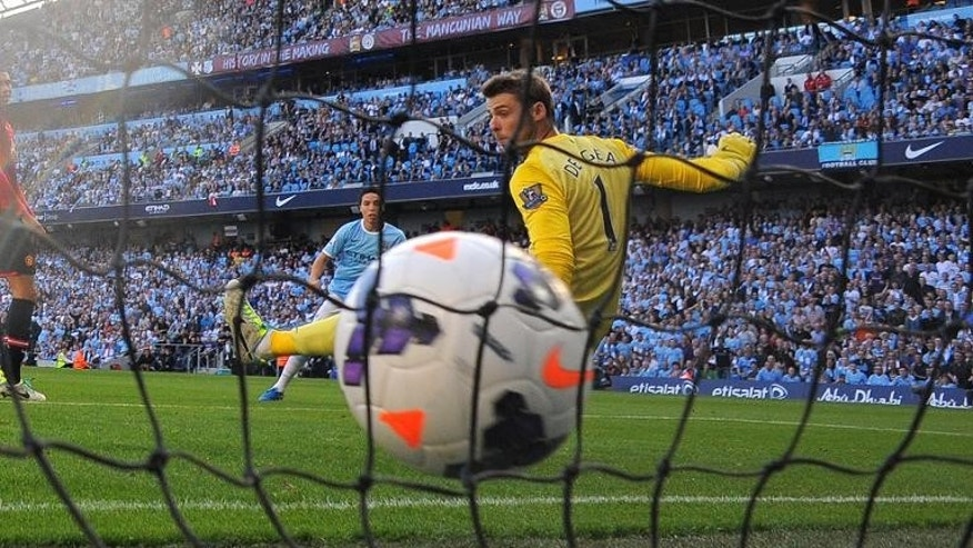 Manchester City midfielder Samir Nasri (back) scores a goal past Manchester United goalkeeper David de Gea during an English Premier League football match at the Etihad Stadium in Manchester on September 22, 2013