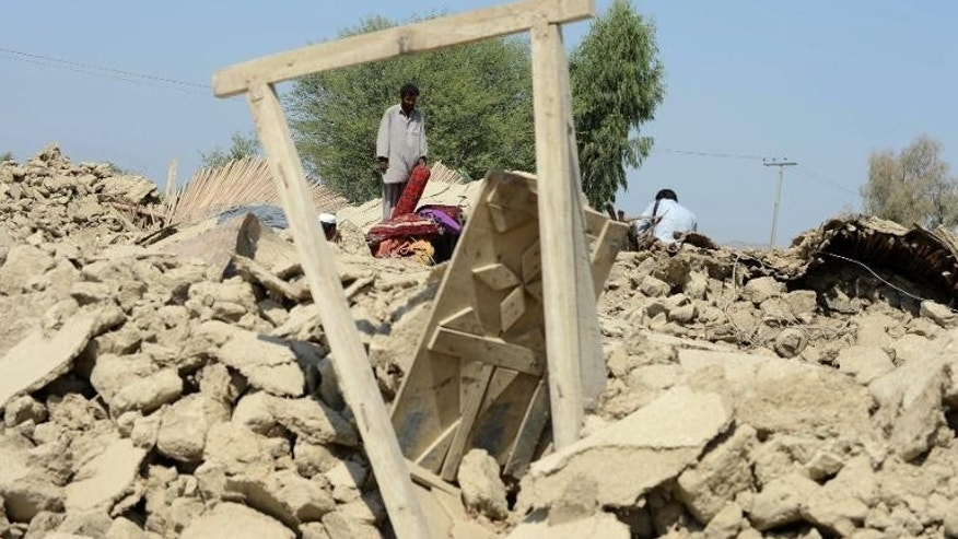 Pakistani villagers gather around their destroyed houses in the earthquake-devastated district of Awaran, on September 25, 2013.
