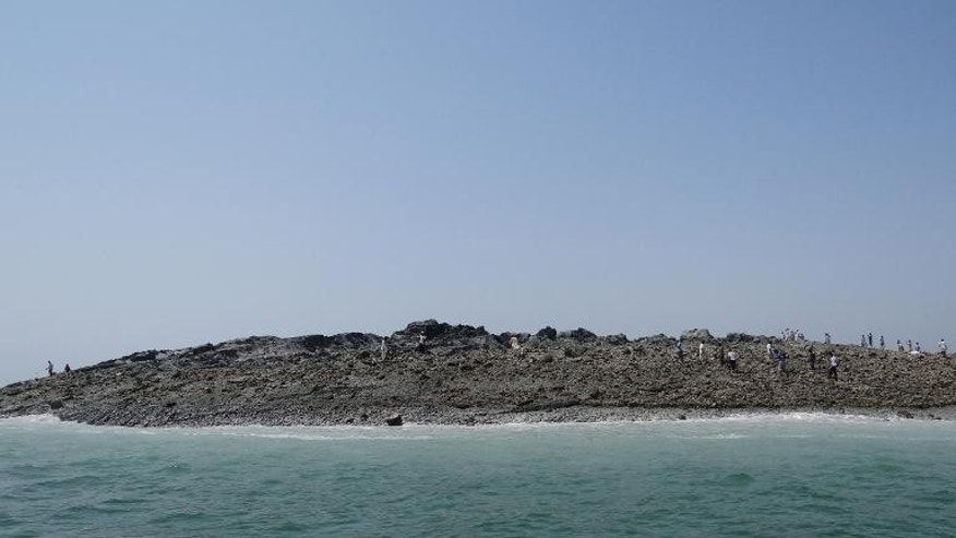 Pakistani men walk on an island that appeared two kilometres off the coast of Gwadar, on September 25, 2013