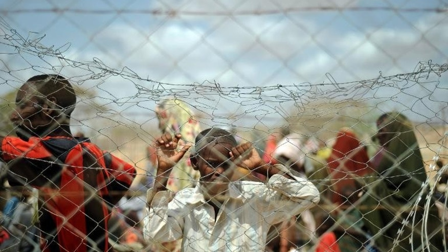 A boy looks through a fence as newly arrived Somali refugees wait outside a registration centre at the Dadaab Refugee camp in eastern Kenya July 23, 2011