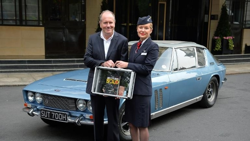"British author William Boyd poses with his new James Bond novel ""Solo"" and British Airways ambassador Helena Flynn during a photo call a day ahead of the its publishing in central London on September 25, 2013."