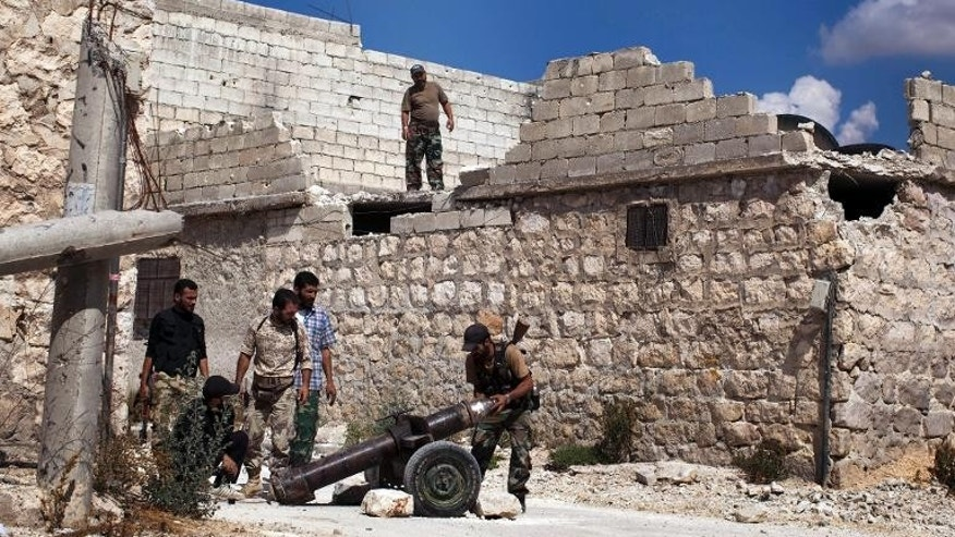 Rebel fighters load a shell into a canon aimed at pro-regime forces in Syria's northern city of Aleppo on September 24, 2013.