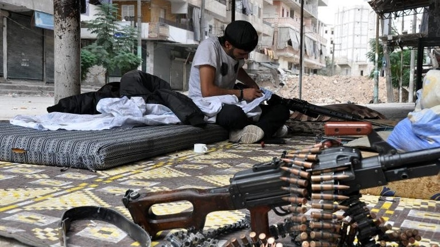 A rebel fighter cleans his weapon in the northern Syrian city of Aleppo on September 20, 2013.