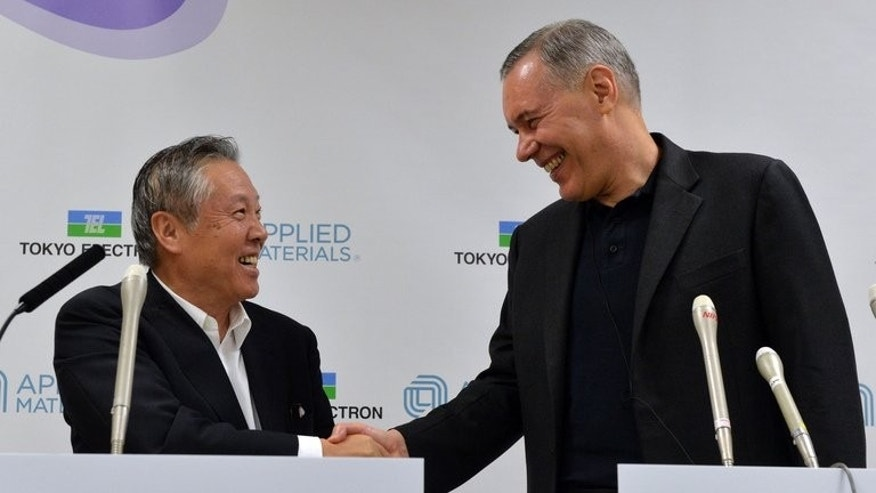 Tokyo Electron chairman Tetsuro Higashi (L) shakes hands with US semiconductor giant Applied Materials CEO Gary Dickerson (R) after they agreed to merge, in Tokyo on September 24, 2013.