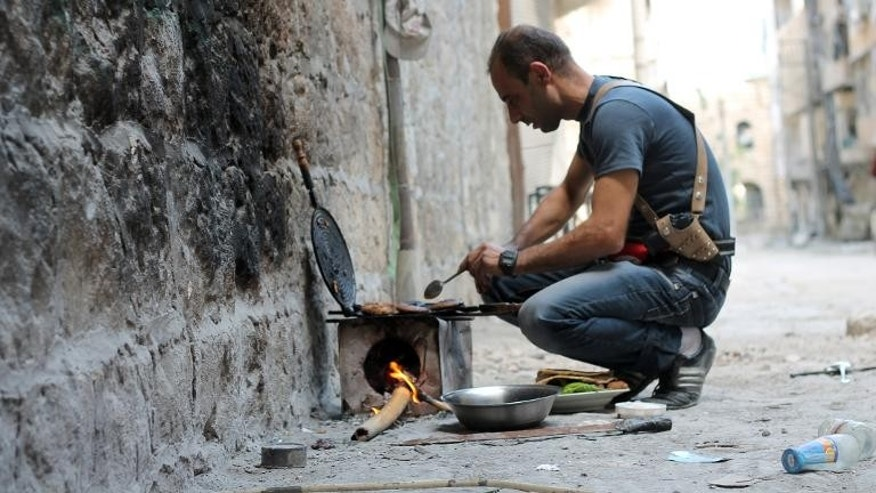 A rebel fighter cooks food on a make-shift stove in Syria's northern city of Aleppo on September 25, 2013.