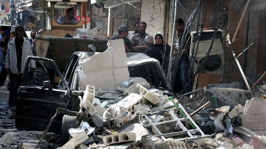 In this photo released by the Syrian official news agency SANA, Syrian citizens gather at the scene of a car bomb exploded in in Damascus, Tuesday September 24, 2013.