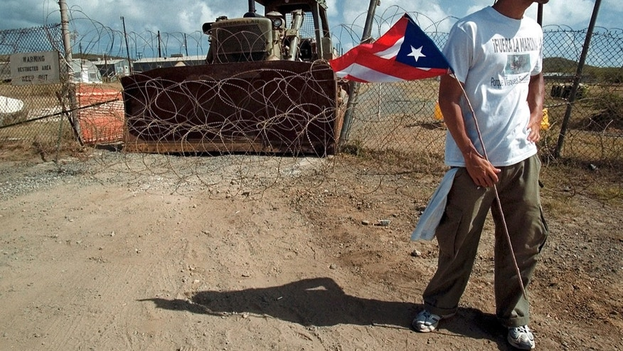 Ismael Guadalupe holds a Puerto Rican flag in front of an entrance to Camp Garcia Naval Base in Vieques, Puerto Rico.