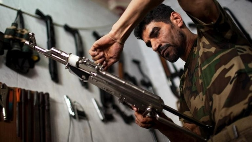 Abu Mohammad, 39, checks an AK47 at his gun shop in the Fardos district of Syria's northern city of Aleppo on September 21, 2013.