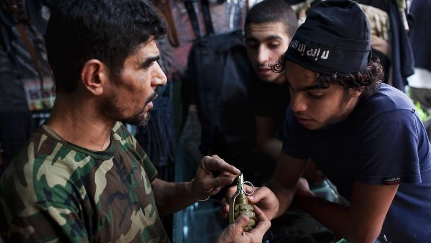 Abu Mohammad, 39, shows a grenade to a client at his gun shop in the Fardos district of Syria's northern city of Aleppo on September 21, 2013.