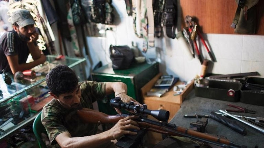 Abu Mohammad, 39, checks a sniper rifle at his gun shop in the Fardos district of Syria's northern city of Aleppo on September 21, 2013.
