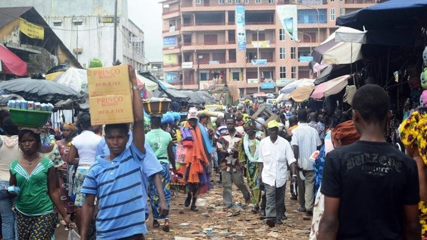 People walk in the street in Conakry on September 24, 2013.