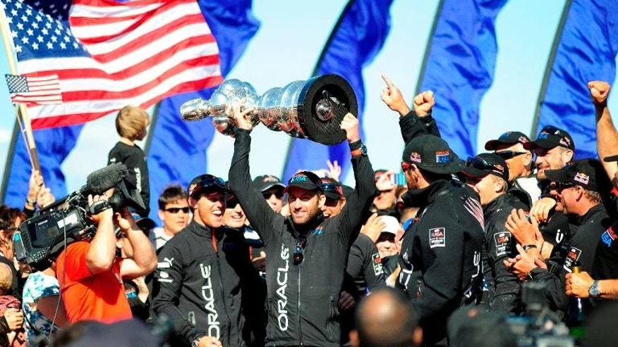 Helmsman Sir Ben Ainslie holds up the America's Cup trophy after Oracle Team USA won the 34th America's Cup on September 25, 2013 in San Francisco