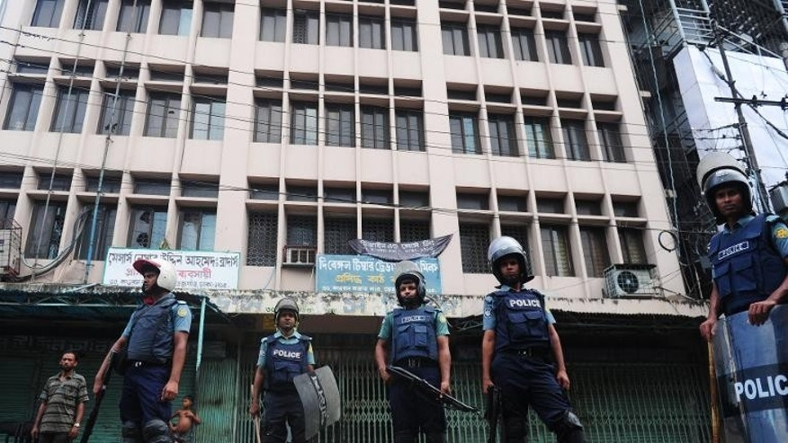 Bangladeshi police stand guard in front of a closed garment factory in Dhaka on September 23, 2013