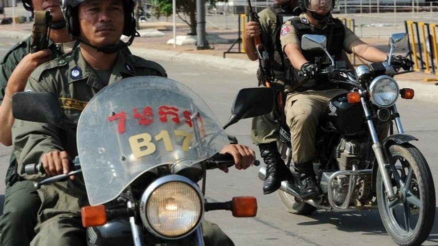 Cambodian police officials ride their motorbikes in Phnom Penh on March 21, 2012