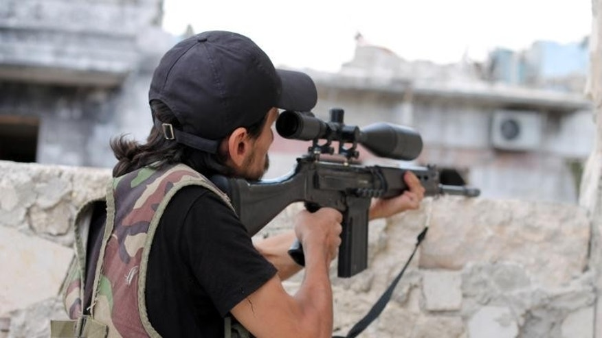 A rebel fighter takes aim at pro-regime forces in Syria's northern city of Aleppo on September 24, 2013.