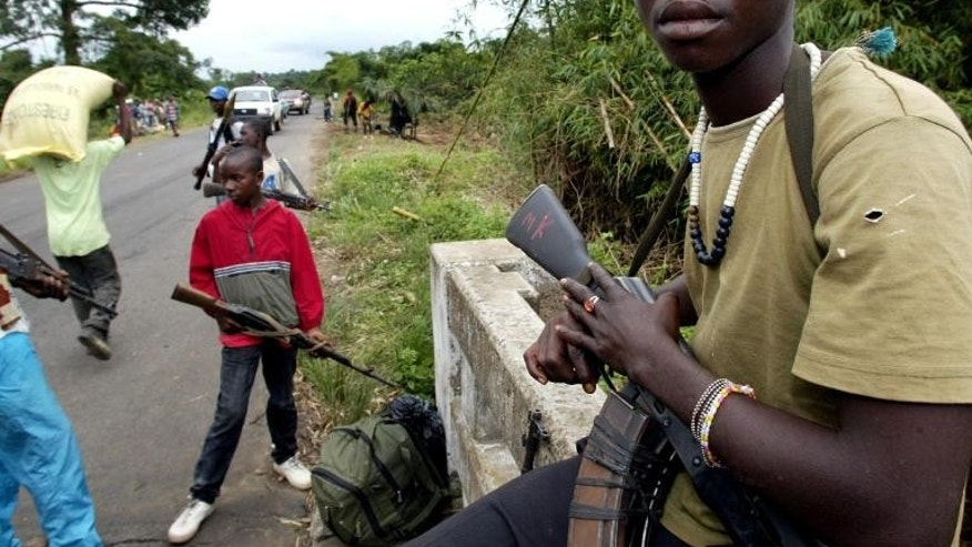 Liberian rebels stand guard at a checkpoint on August 19, 2003 near Monrovia.
