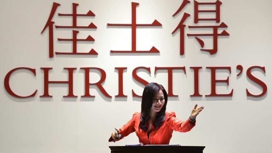 Auctioneer Jin Ling takes bids at a Christie's auction in Shanghai, on September 26, 2013.