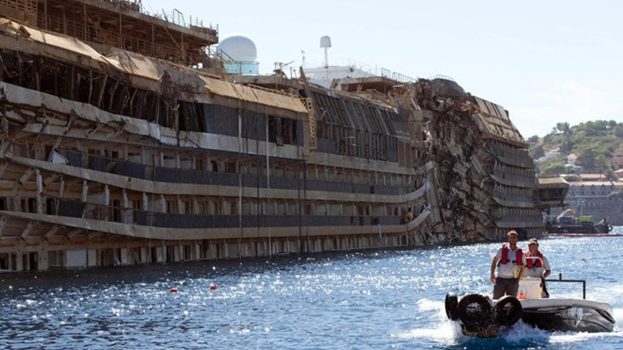 Sept. 18, 2013: People take a small boat past the damaged side of he Costa Concordia  on the Tuscan Island of Giglio, Italy. The crippled cruise ship was pulled completely upright early Tuesday after a complicated, 19-hour operation to wrench it from its side where it capsized last year off Tuscany.