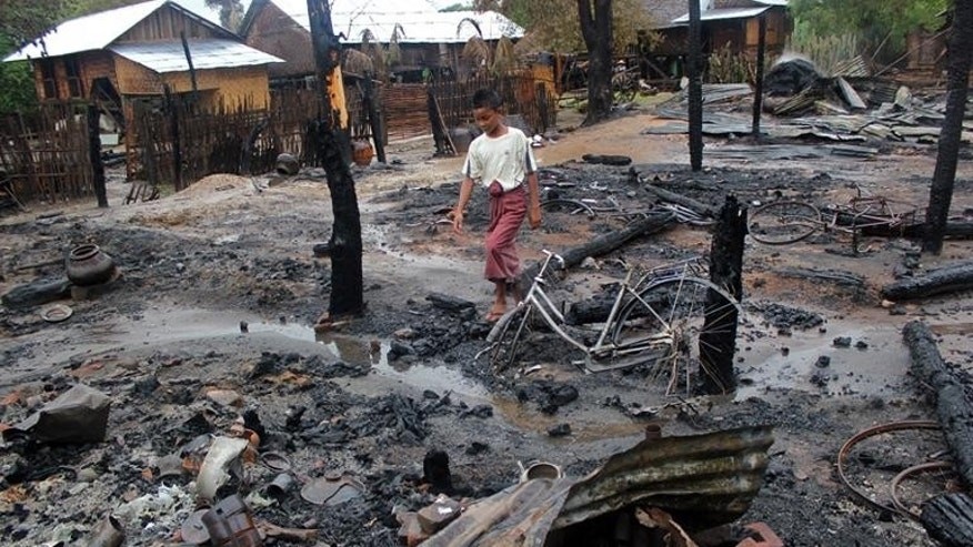 A Muslim boy walks through the charred remains of houses in Htan Gone village on August 26, 2013, after some 1,000 anti-Muslim rioters rampaged through villages in Kanbalu township in Myanmar.