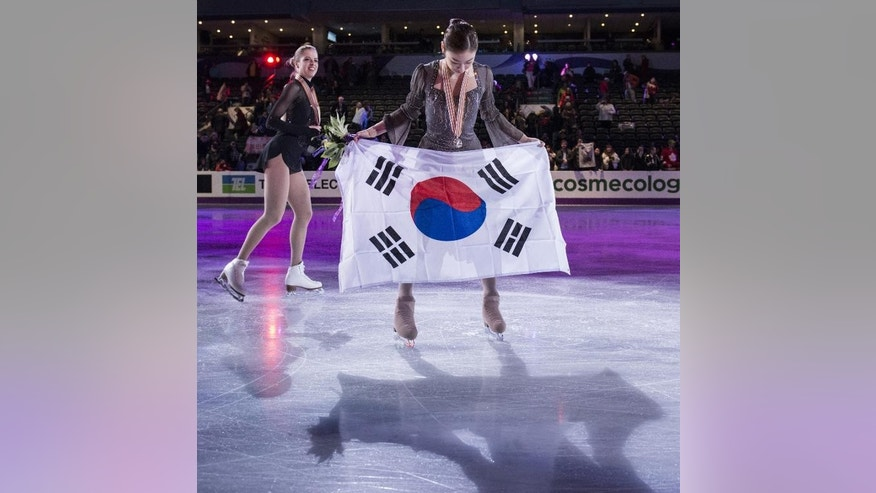 Gold medalist Kim Yu-na of South Korea displays the South Korean national flag at the 2013 World Figure Skating Championships in London, Ontario, March 16, 2013