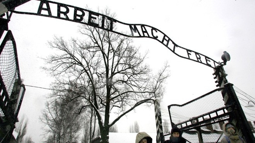 "In a Jan. 26, 2005 file photo, visitors walk under the notorious ""Arbeit Macht Frei"" sign  at  the entrance gate of the Auschwitz Nazi concentration camp in Oswiecim, southern Poland."