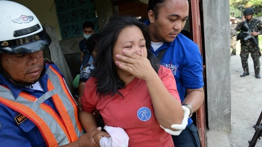 An injured resident is helped by rescuers after a mortar shell believed to be from the Muslim rebels' position hit her house in Zamboanga, on September 21, 2013.