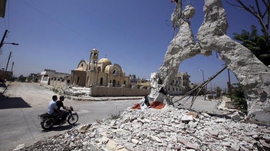 Men ride a motorbike past the remains of a building on August 1, 2013 in front of Saint Elie Church in Qusayr, in Syria's central Homs province.