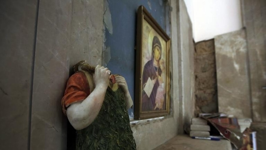 A picture taken on August 1, 2013 shows a vandalized statue at Saint Elie Church in Qusayr, in Syria's central Homs province.