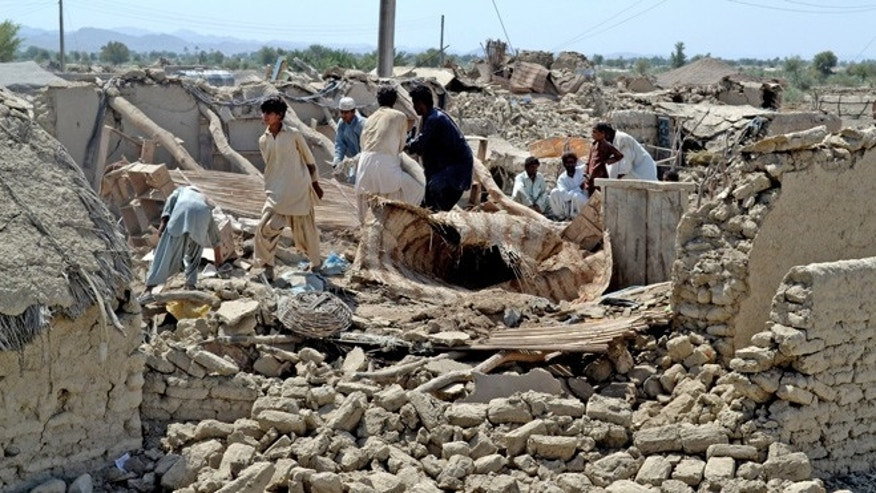 Sept. 25, 2013: Pakistani villagers look for belongings amid the rubble of their destroyed homes following an earthquake in the remote district of Awaran, Baluchistan province, Pakistan. Rescuers struggled Wednesday to help thousands of people injured and left homeless after their houses collapsed in a massive earthquake in southwestern Pakistan on Tuesday.