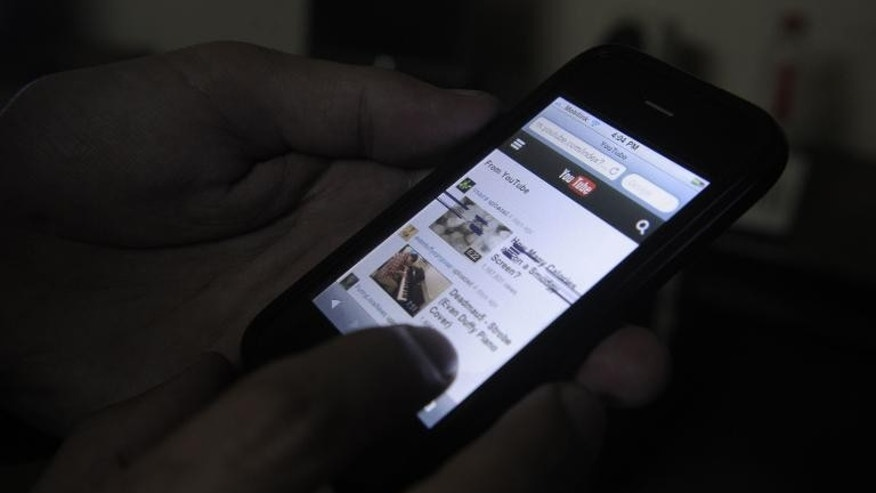 A Pakistani cell phone user browses YouTube on his mobile phone in Quetta on December 29, 2012