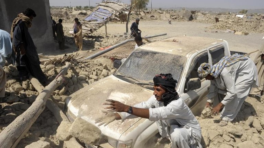 Pakistani survivors clear the debris of destroyed houses in the earthquake-devastated district of Awaran, on September 25, 2013. The death toll from the earthquake has soared to around 350 people with more than 500 injured.