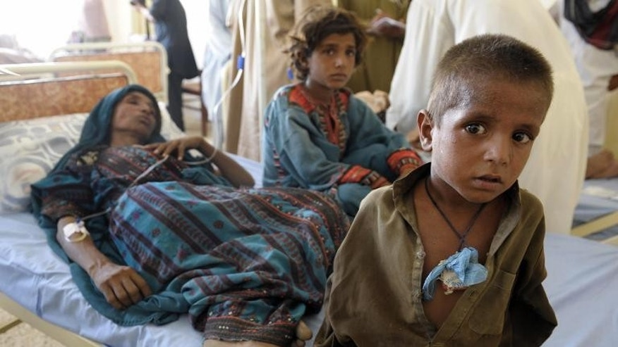 An injured Pakistani survivor is surrounded by her children at a makeshift hospital in the earthquake-devastated district of Awaran, on September 25, 2013.