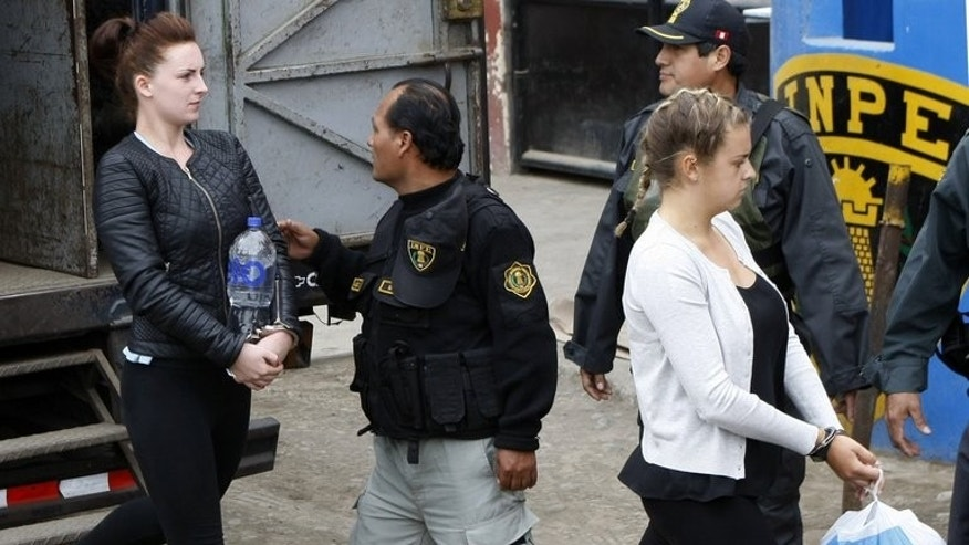Irish national Michaella McCollum (L) and Briton Melissa Reid walk into the Sarita Colonia Jailhouse Court in Callao, Lima, on September 24, 2013, where both pleaded guilty to attempting to sneak 11 kilos of cocaine out of the country and into Spain