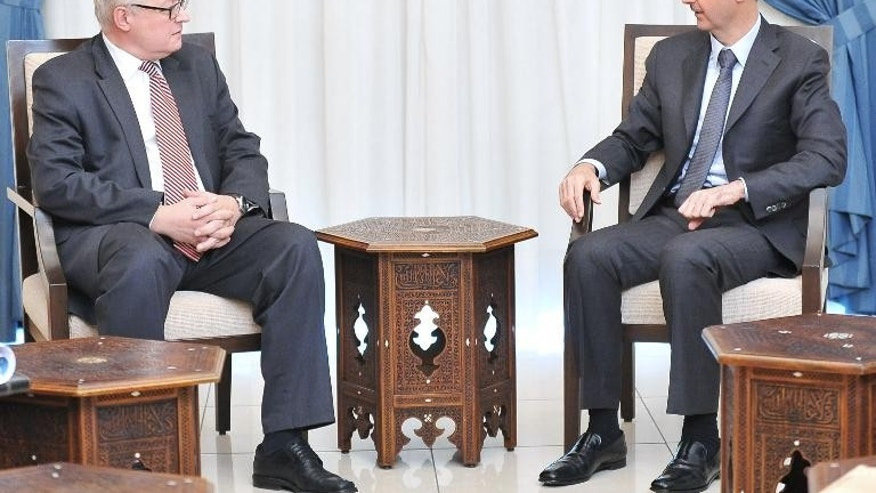 A handout picture released by SANA on September 18, 2013 shows Russian Deputy Foreign Minister Sergei Ryabkov (L) with Syrian President Bashar al-Assad in Damascus.