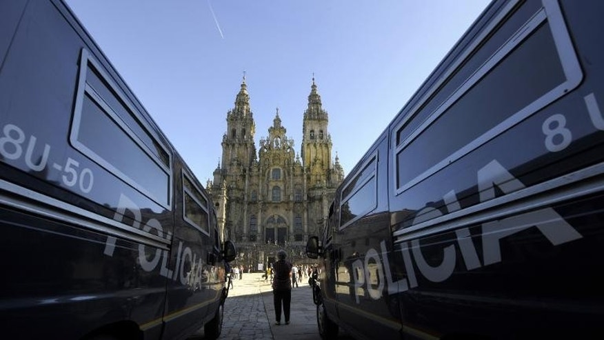 A woman stands between two police vans parked at the Obradoiro Square, in front of the Santiago de Compostela Cathedral, on November 4, 2010