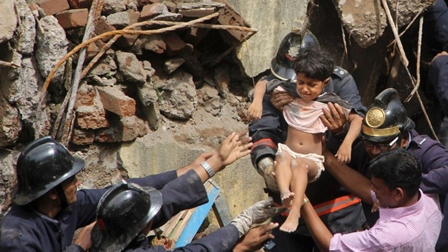 Sept. 27, 2013: Indian Fire officials rescue a girl from debris of a collapsed building in Mumbai, India. The multi-story residential building collapsed in India's financial capital of Mumbai early Friday, killing at least three people and sending rescuers racing to reach dozens of people feared trapped in the rubble. (AP Photo)