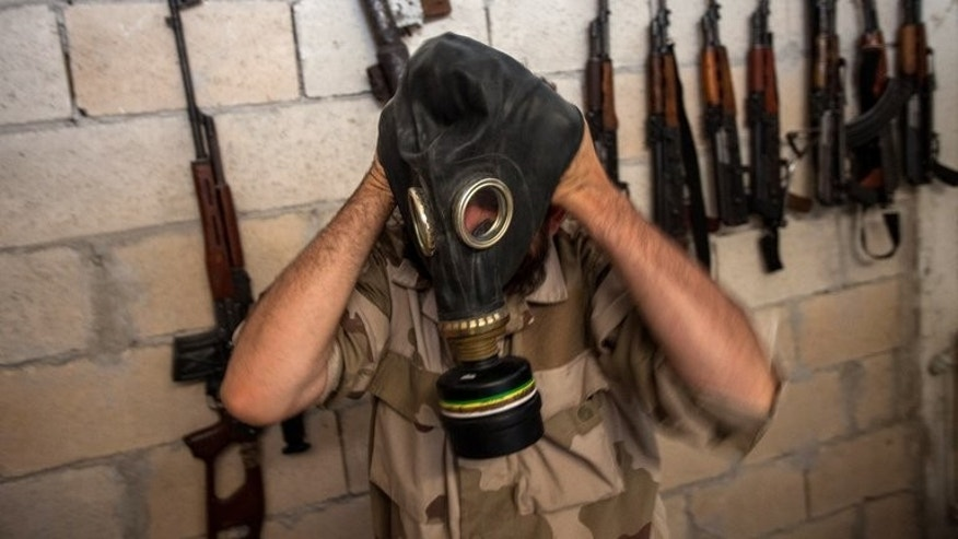 A Syrian rebel tries on a gas mask in the northwestern province of Idlib, on July 18, 2013