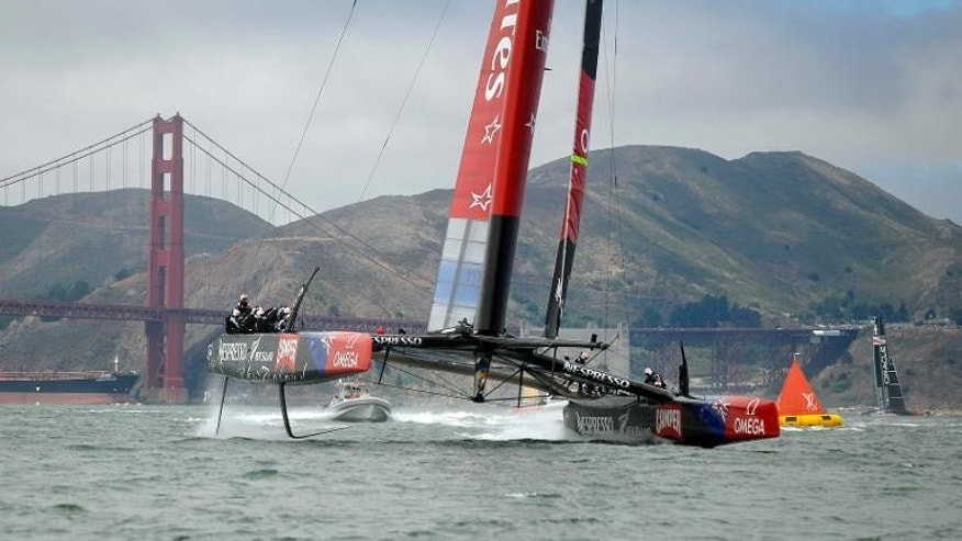Team Emirates New Zealand (L), and Team Oracle USA sail near the Golden Gate Bridge during a training session for the America's Cup race in San Francisco, on July 17, 2013