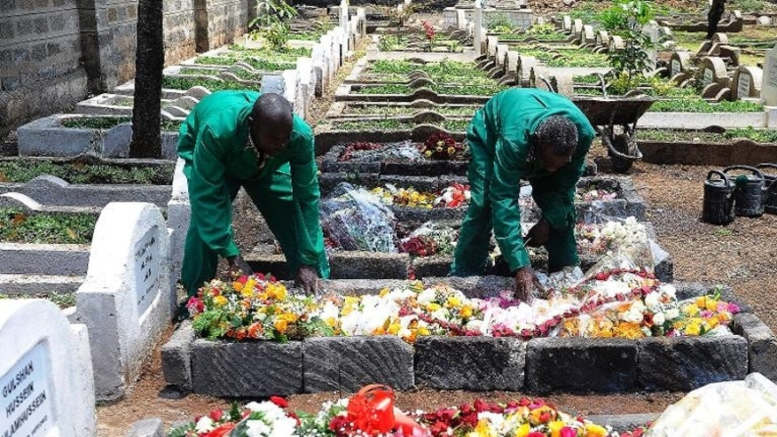 Workers at the Shia Imami Ismailia cemetry arrange flowers on September 26, 2013 on the grave of Kenyan journalist Ruhila Adatia-Sood during her funeral ceremony in Nairobi