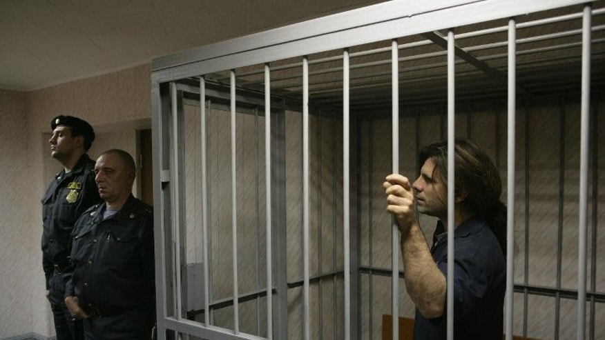 British ship's engineer Iain Rogers stands in the defendant's cage at the Leninsky district court in Murmansk on September 26, 2013, in a photo provided by Greenpeace