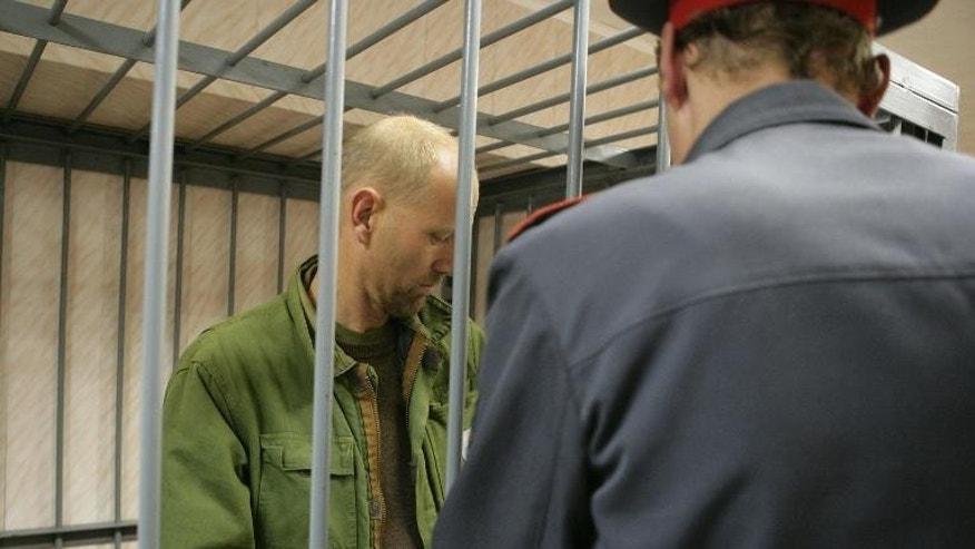 British logistics co-ordinator Frank Hewetson from the United Kingdom stands in a defendant's cage in a court in the northern Russian city of Murmansk on September 26, 2013, in a photo provided by Greenpeace