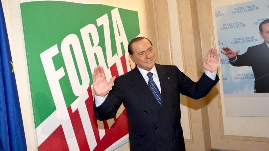 Italy's former prime minister Silvio Berlusconi poses for photographers during the inauguration of the new PDL party headquarters, in Rome, on September 19, 2013.