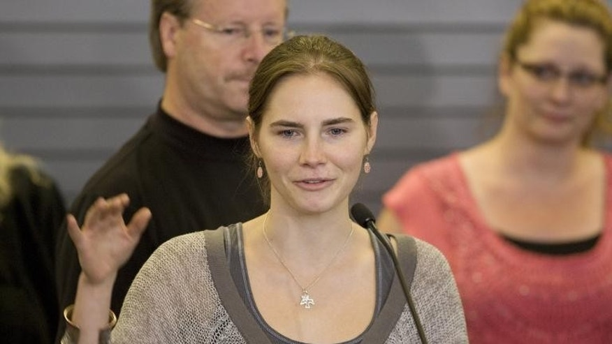 Amanda Knox waves to supporters as she makes her first appearance at SeaTac Airport after arriving in Seattle following her release from prison in Italy on October 4, 2011