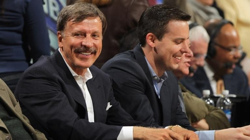 Stan Kroenke (L) along with his son Josh Kroenke atch from courtside seats as the Denver Nuggets host the San Antonio Spurs at the Pepsi Center in Denver, Colorado on on March 23, 2011.