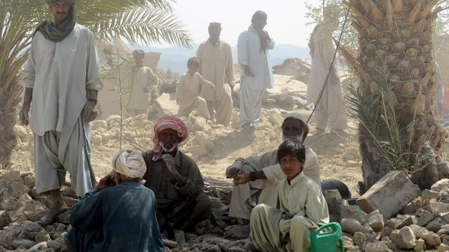 Pakistani earthquake survivors rest near their collapsed mud houses in the earthquake-devastated district of Awaran on September 25, 2013.