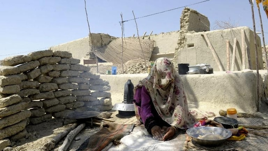 A Pakistani earthquake survivor prepares bread alongside her partially-collapsed mud house at Labach area, in the earthquake-devastated district of Awaran on September 26, 2013.