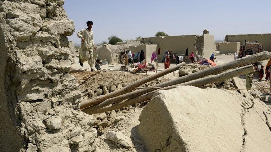 A Pakistani earthquake survivor walks on the debris of collapsed mud houses at Labach area, in the earthquake-devastated district of Awaran on September 26, 2013.