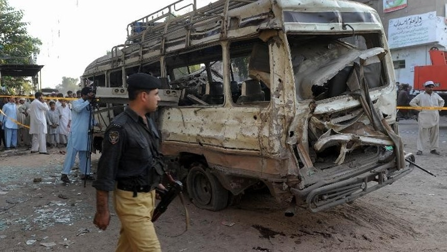 A Pakistani policeman walks past the wreckage of a passenger bus following an explosion in Peshawar, on September 19, 2012