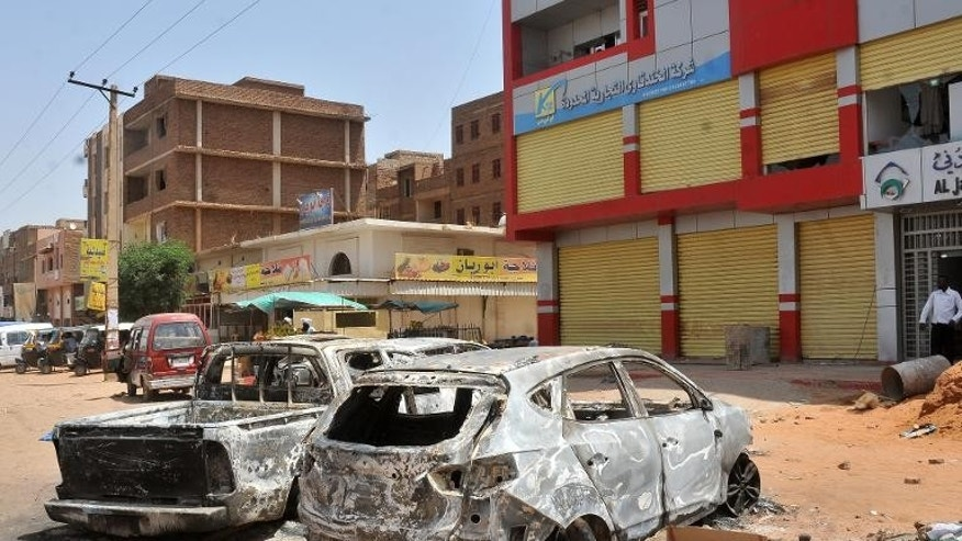 A picture taken on September 26, 2013 shows burnt vehicles in a street of the Sudanese capital Khartoum after rioting erupted following a decision by the government to scrap fuel subsidies